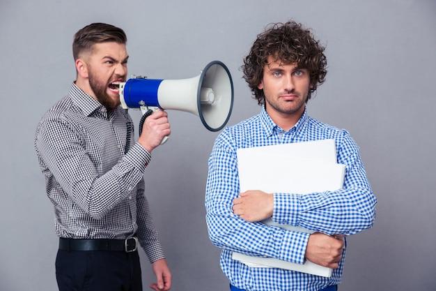 Uomo d'affari arrabbiato che grida tramite il megafono a un altro uomo sopra il muro grigio