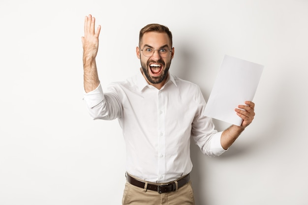 Uomo d'affari arrabbiato che grida e che mostra cattivo rapporto, che sembra deluso e frustrato, in piedi su sfondo bianco.