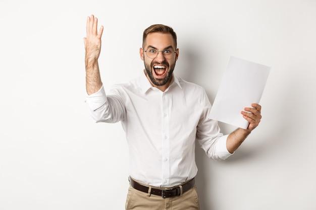 Uomo d'affari arrabbiato che grida e mostra un cattivo rapporto, sembra deluso e frustrato, in piedi su sfondo bianco