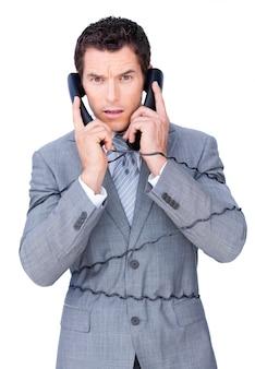 L'uomo d'affari arrabbiato si aggroviglia in su nei cavi del telefono