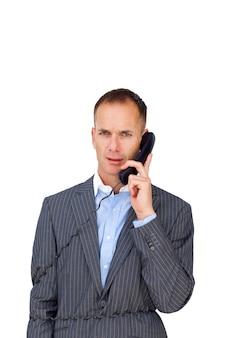 Uomo d'affari arrabbiato aggrovigliato nei fili del telefono