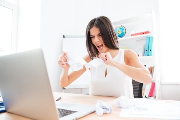 Donna d'affari arrabbiata che lavora con laptop e documenti in ufficio