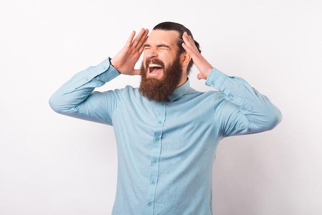 L'uomo disperato arrabbiato sta avendo un forte mal di testa. foto realizzata su sfondo bianco.