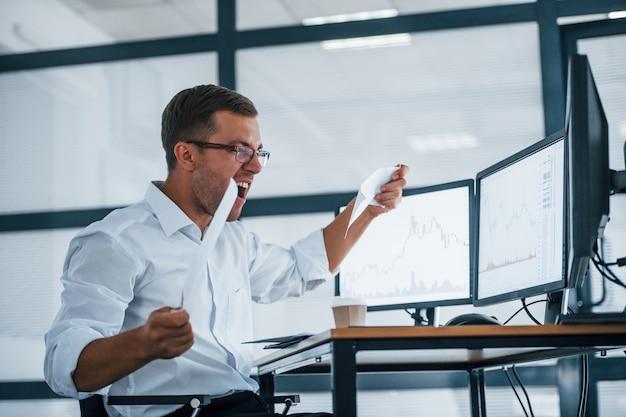 L'impiegato arrabbiato getta la carta concezione del fallimento. il giovane uomo d'affari in abiti formali è in ufficio con più schermi.