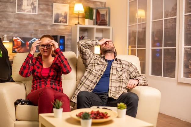 Giocatori arrabbiati e frustrati che perdono mentre giocano ai videogiochi in salotto a tarda notte