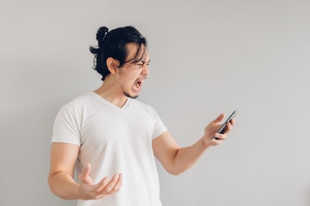 L'uomo arrabbiato e furioso capelli lunghi in maglietta bianca sta usando smartphone.