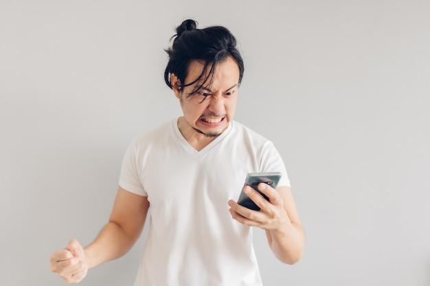 L'uomo arrabbiato e furioso capelli lunghi in maglietta bianca sta utilizzando lo smartphone