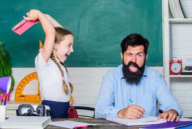 La ragazza arrabbiata odia leggere il libro. di nuovo a scuola. insegnamento privato. bambina piccola con uomo insegnante barbuto in aula. lezioni private. giornata della conoscenza. scuola a domicilio. la figlia studia con il padre.
