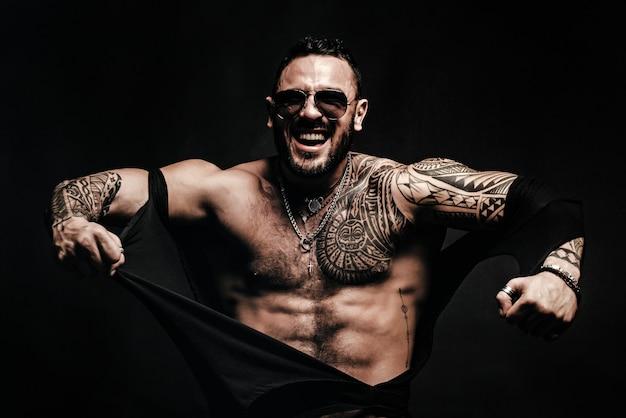 Ragazzo arrabbiato alla moda ragazzo brutale con una camicia strappata dal corpo sexy uomo sexy con un corpo muscoloso e il torso nudo