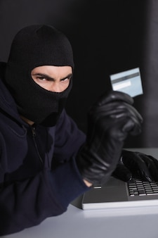 Pirata informatico arrabbiato con carta di credito e laptop