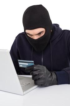 Pirata informatico arrabbiato che utilizza computer portatile e carta di credito
