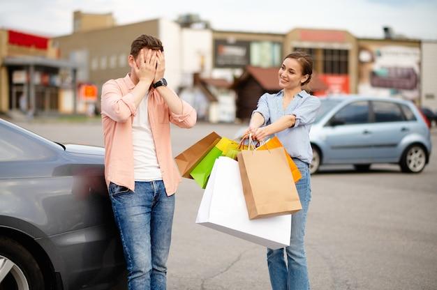 Il marito arrabbiato non vuole portare borse, parcheggiare