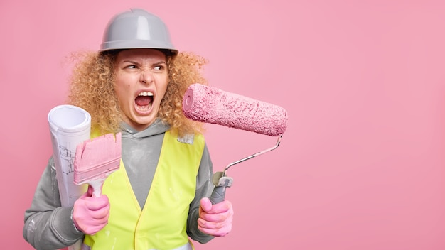 Una lavoratrice edile arrabbiata e irritata tiene in mano l'attrezzatura da costruzione e il progetto indossa un elmetto protettivo e indumenti di sicurezza