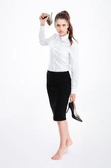 Giovane donna d'affari irritata arrabbiata in piedi e lanciando scarpe con tacchi alti sul muro bianco white