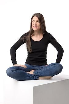Giovane donna arrabbiata e irritata che si siede nella posa del loto sul cubo bianco. immagine isolata sul muro bianco.