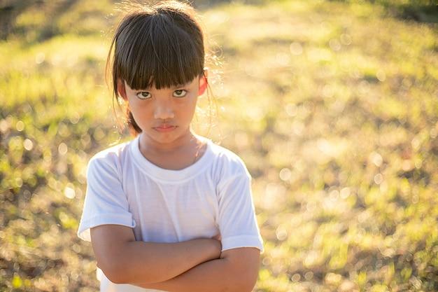 Bambina arrabbiata sullo sfondo del giardino, sul segno e sul concetto di gesto