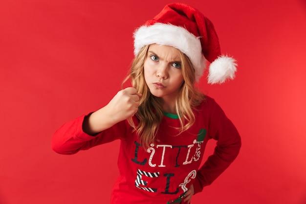 Bambina arrabbiata che indossa il cappello di natale in piedi isolato, mostrando il suo pugno