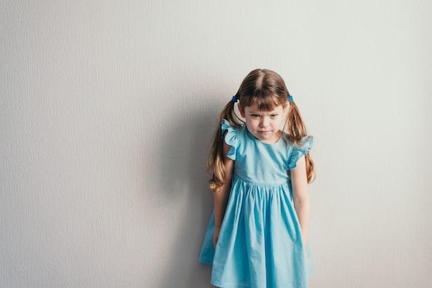 Bambina bianca arrabbiata in vestito blu su backgroung neutro
