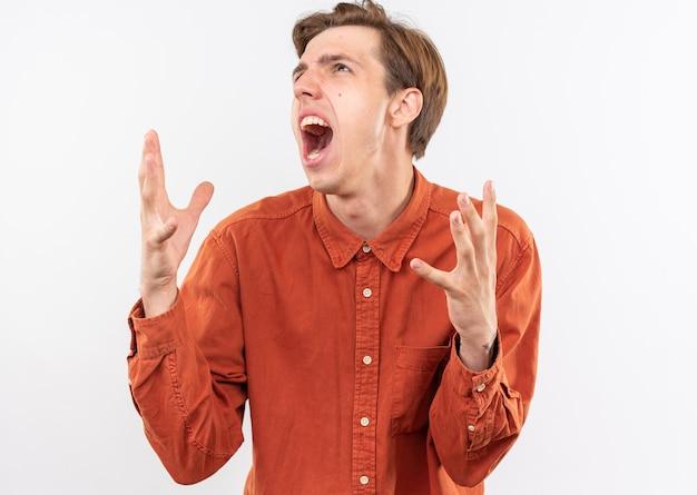 Arrabbiato guardando il giovane bel ragazzo che indossa una camicia rossa allargando le mani