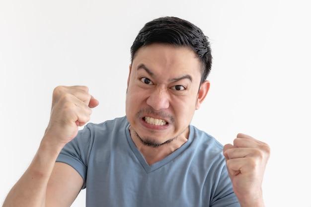 Faccia arrabbiata e pazza dell'uomo asiatico in maglietta blu su spazio isolato.
