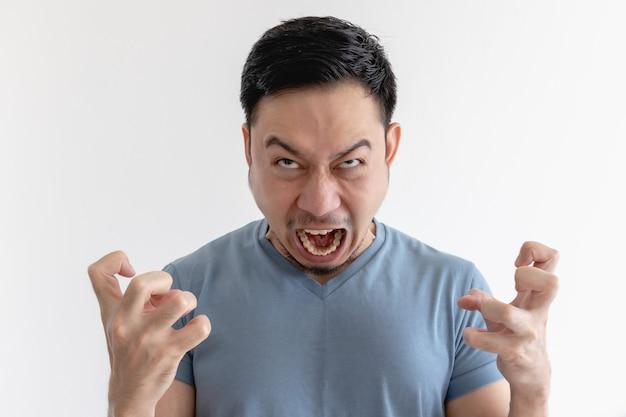 Faccia arrabbiata e pazza dell'uomo in maglietta blu sulla parete isolata.