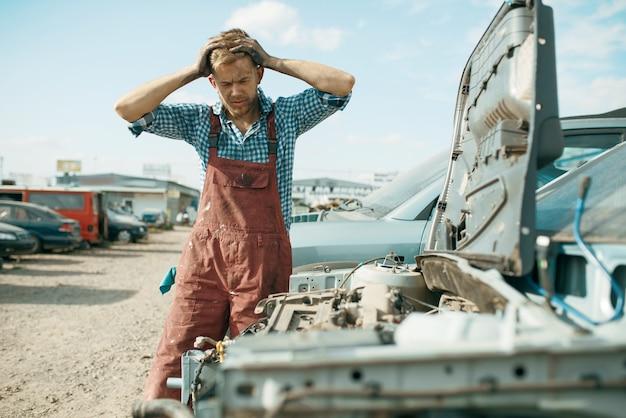 Il riparatore maschio arrabbiato lavora alla discarica di auto. rottami di automobili, rifiuti di veicoli, rifiuti di automobili, trasporti abbandonati, danneggiati e frantumati