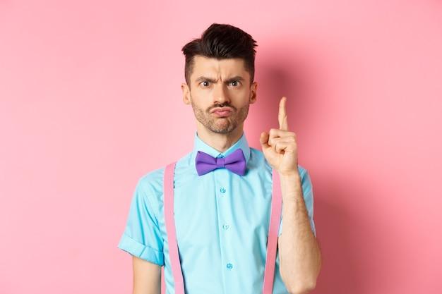 Insegnante maschio arrabbiato che agita il dito e rimprovera qualcuno che si comporta male, accigliato scontroso e lezione di insegnamento, in piedi su sfondo rosa