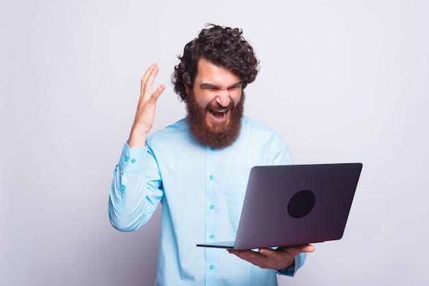Uomo arrabbiato in camicia blu che ha problemi al lavoro, uomo che grida al computer portatile