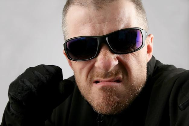 Uomo arrabbiato con gli occhiali scuri