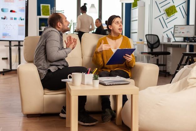 Manager di uomo arrabbiato che discute dipendente donna per cattivo risultato di lavoro, seduto sul divano, mentre diversi colleghi che lavorano spaventati in background
