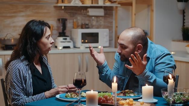 Uomo arrabbiato per test di gravidanza positivo durante una cena romantica. donna che sorprende suo marito incinta, infelice, nervoso, partner, bambino indesiderato, frustrato per i risultati.