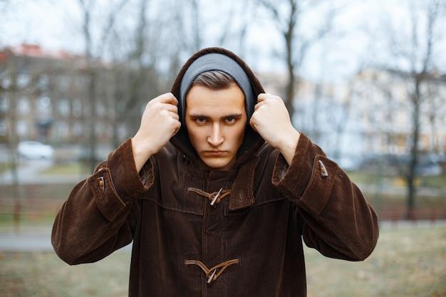L'uomo arrabbiato mette la cappa sul parco d'autunno