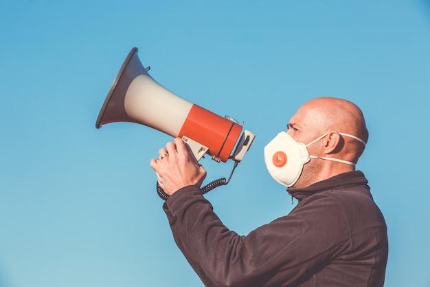 Uomo arrabbiato con maschera medica che urla nel megafono, coronavirus, protesta covid-2019, crisi economica, pandemia mondiale