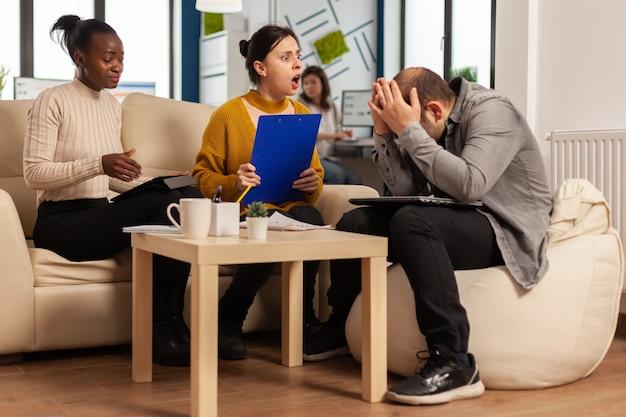 Donna manager arrabbiata che discute in disaccordo su un cattivo contratto d'affari, diversi colleghi che litigano sul documento seduto sul divano alla scrivania dell'ufficio, partner che gridano la rottura dell'accordo
