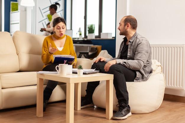 Donna arrabbiata del manager che urla al dipendente uomo che non è d'accordo sul cattivo contratto d'affari seduto sul divano alla scrivania dell'ufficio