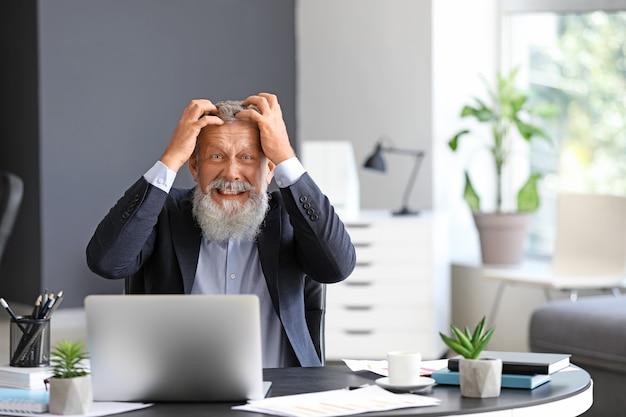 Uomo maturo arrabbiato che lavora in ufficio