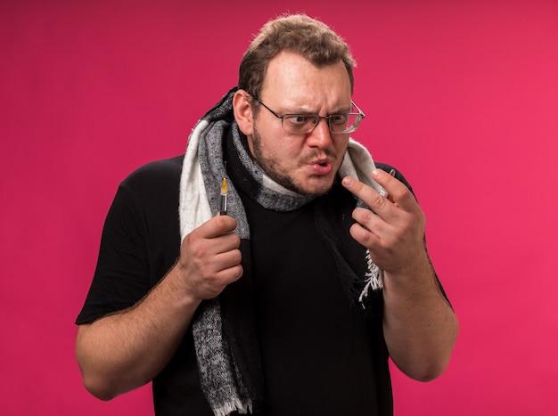 Maschio malato di mezza età arrabbiato che indossa una sciarpa che tiene la siringa guardando l'ampolla in mano