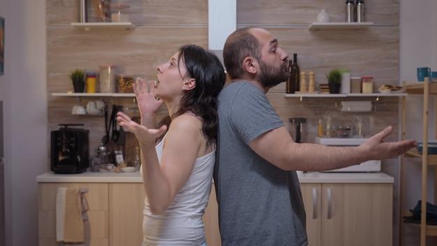 Persone arrabbiate che discutono in piedi schiena contro schiena. coppia infelice furiosa, irritata, frustrata, gelosa che urla accusandosi a vicenda di litigare con la famiglia seduta in cucina.