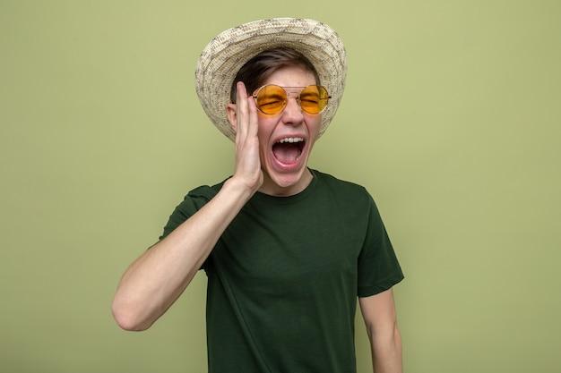 Arrabbiato mettendo la mano sulla guancia giovane bel ragazzo che indossa un cappello con gli occhiali