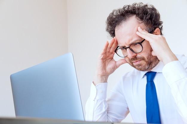 Uomo d'affari triste arrabbiato in una camicia bianca e cravatta tenendo la testa sotto shock e guardando il computer. il concetto di fallimento, la crisi economica