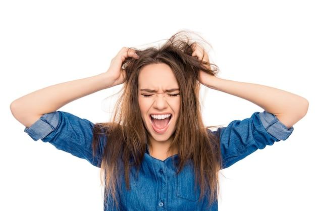 Giovane donna triste arrabbiata con capelli danneggiati che grida