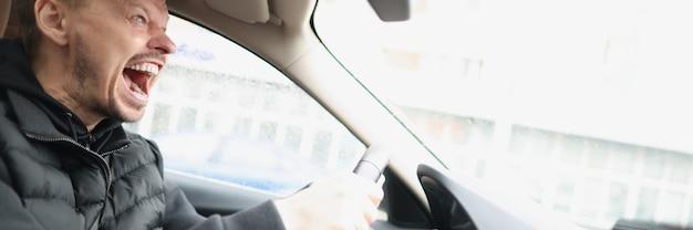 Autista maschio di grido arrabbiato che guida il primo piano dell'automobile