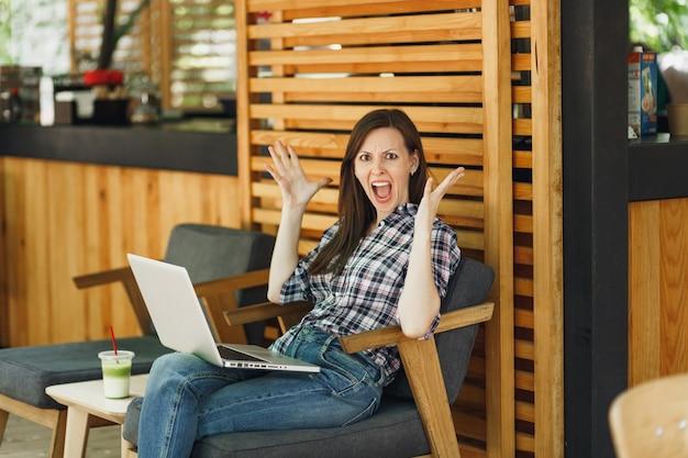 Ragazza arrabbiata urlante triste sconvolta nella caffetteria in legno della caffetteria all'aperto che si siede con un moderno computer portatile, allargando le mani durante il tempo libero. ufficio mobile