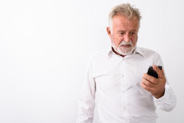 Uomo barbuto anziano arrabbiato utilizzando il telefono cellulare su bianco