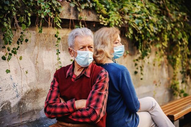 Coppia senior arrabbiata con maschere protettive sulla seduta sulla panchina schiena contro schiena.