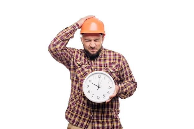 Operaio arrabbiato e scioccato del costruttore nel casco arancione della costruzione protettiva che tiene in mano una grande sveglia isolata su fondo bianco. ora di lavorare. tempo di costruzione dell'edificio.