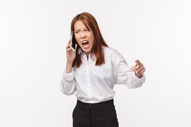 Giovane donna asiatica arrabbiata e tesa, aggressiva che impreca come parlare al telefono, pugno serrato indignato urlando in dinamica mobile da rabbia e irritazione, muro bianco, affrontare qualcuno