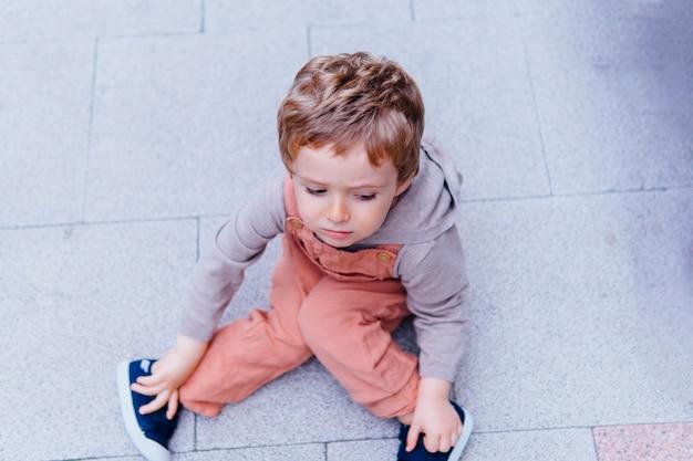 Un bambino di tre anni arrabbiato seduto sul pavimento che si rifiuta di andare a casa con un capriccio