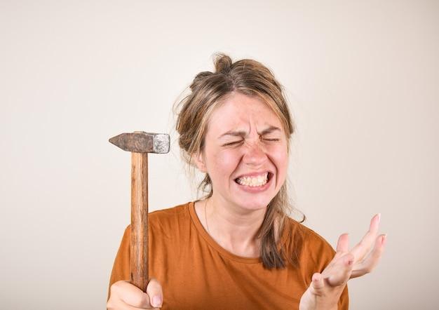 Donna arrabbiata che tiene un martello tra le mani, incapace di fare riparazioni in casa. una donna con un martello è arrabbiata perché non può fare riparazioni.