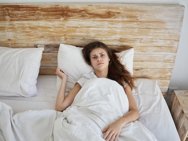 La donna arrabbiata giace a letto sotto la coperta vista dall'alto del mattino